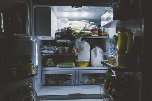 Picture of a refrigerator packed with various contents, including milk.